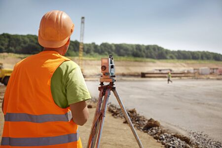 geodesist: Builder in orange helmet and vest on a building place
