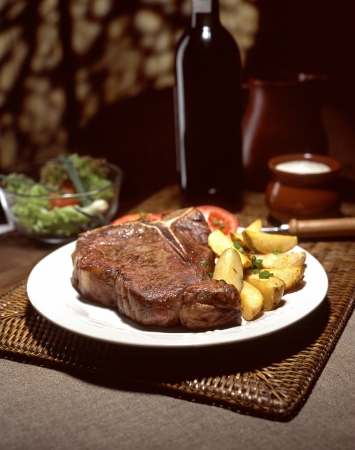 tasty steak with bottle of wine, salad and cream sauce Stock Photo