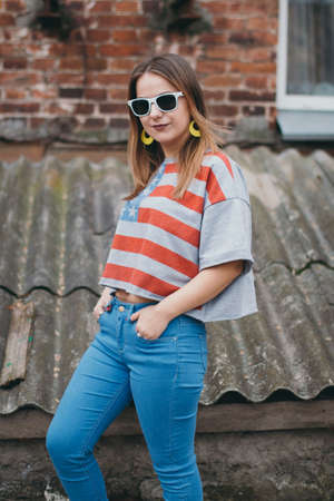 A hipster girl in an old courtyard posing and smiling Stock Photo