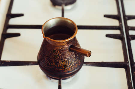 Turka with coffee on the gas stove. Stock Photo