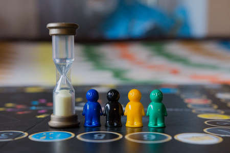 Multi-colored chips for tabletop game in the form of little men and an hourglass.
