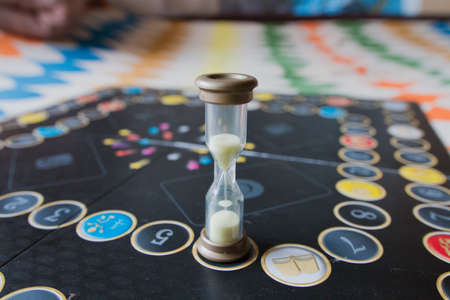 double game: Hourglass on the playing field for board games. Stock Photo