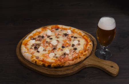 Hot piece of pizza with melted cheese on a rustic wooden table and beer.
