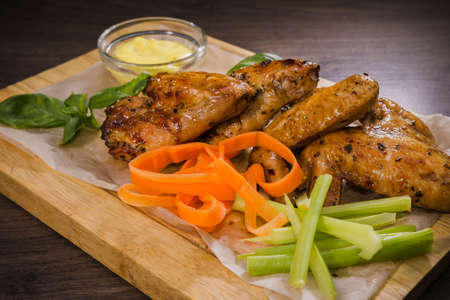 Fried chicken wings with sauce and salad.