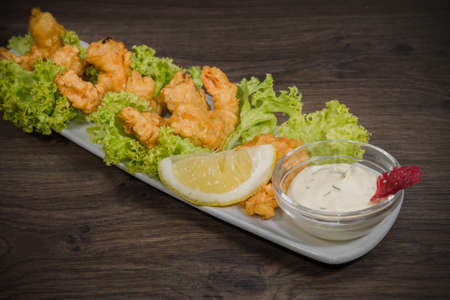 Fried prawns on a plate with sauce and on a wooden background.