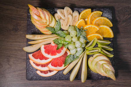 Fruit slicing on a wooden background and on a stone stand.