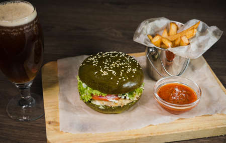 Green burger with fried potatoes and tomato sauce on a wooden stand with a glass of beer.