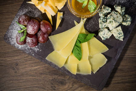 Cheese mix with honey and grapes on a stone background.