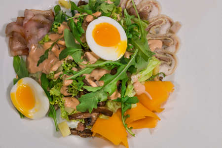 Salad with egg and mushrooms on a white plate and a wooden background.