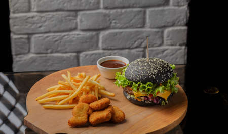 Black burger on a wooden background with potatoes and sauce Banque d'images - 101810984