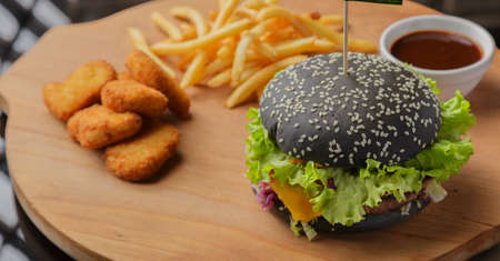 Black burger on a wooden background with potatoes and sauce Banque d'images - 101811047