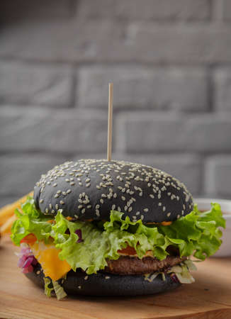 Black burger on a wooden background with potatoes and sauce Banque d'images - 101811051