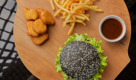 Black burger on a wooden background with potatoes and sauce Banque d'images - 101811052
