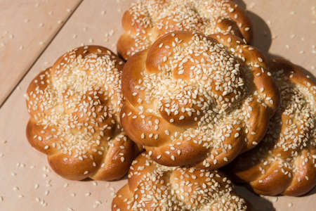 Buns with sesame seeds on a wooden background
