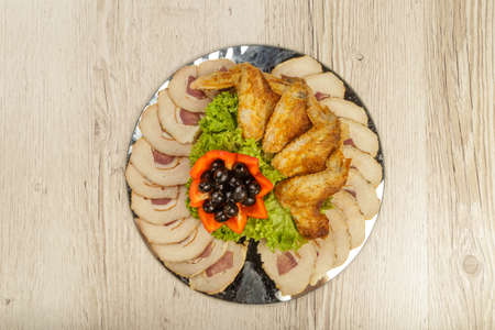 Dish from tartlets chicken wings and meat sliced with the presence of lettuce leaves. Stock Photo