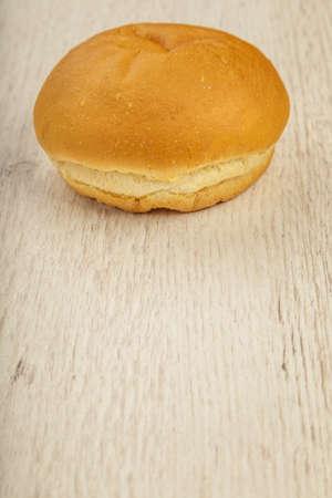 Fresh ruddy bun on a wooden background. Stock Photo