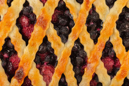 Berry pie on a wooden background with ingredients.