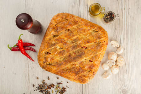 Meat pie on a wooden background with ingredients. 免版税图像