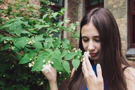 A very beautiful and cheerful girl stands on the street near a bush with white flowers 版權商用圖片