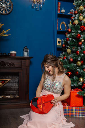 Very beautiful and happy girl sitting on the sofa in the New Years room and opens a gift. Stock Photo