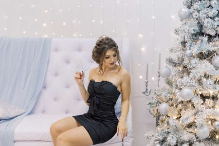 Very beautiful woman drinking champagne in new year decor. Stock Photo
