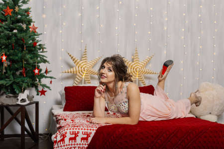 Very beautiful and sexy woman on the bed in the New Years decor. Stock Photo