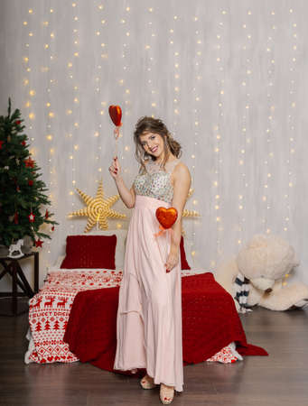 Very beautiful and sexy woman on the bed in the New Years decor with hearts in their hands.