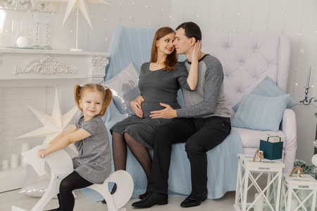 Happy and beautiful family of three at a festive bright New Years room. Stock Photo