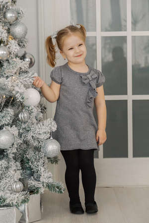 A little girl is standing by a Christmas tree and touching toys.