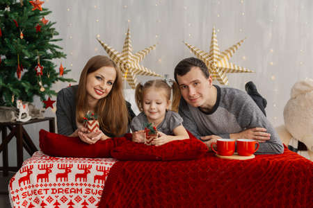 Happy family on bed on a bright Christmas morning. New Year 2019. Stock Photo