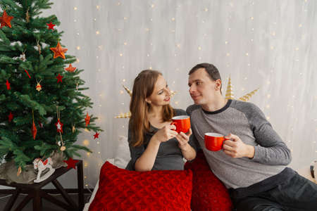 Family couple on the bed in the New Years room holding red mugs with tea. Stock Photo