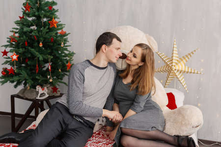 Very beautiful girl and husband on the bed with a bear in the Christmas room. Imagens