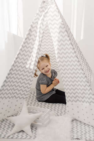A girl plays in a tepee with toys.