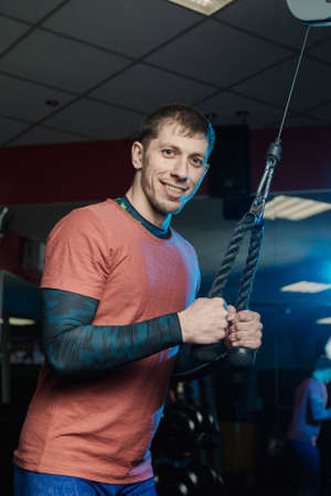 Handsome athletic man trains triceps on the block in the gym.