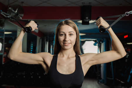 Active beautiful fitness model girl trains biceps on the block in the gym.