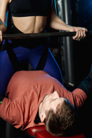 Female trainer helping guy to train in the gym Bar Bench Press.