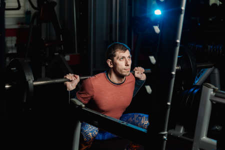 Handsome athletic man doing a squat in the gym.