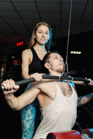 Active beautiful fitness model girl helps young man to train on the block simulator in the gym.