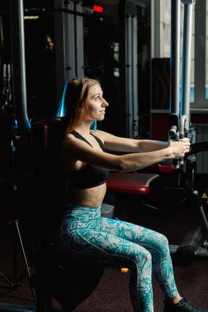 Active beautiful fitness model girl trains pectoral muscles on a simulator in the gym. Stock Photo