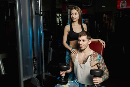 Active beautiful fitness model girl helps to train with dumbbells while sitting to her boyfriend in the gym.
