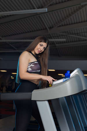 Attractive young sports woman is working out in gym. Doing cardio training on curve treadmill. Running on non-motorized treadmill. 免版税图像