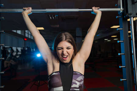 Beautiful sexy fitness model shakes a barbell sitting from behind the head in the gym. Stock Photo