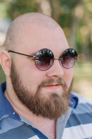 .Young man with round glasses and overweight in the park. Archivio Fotografico