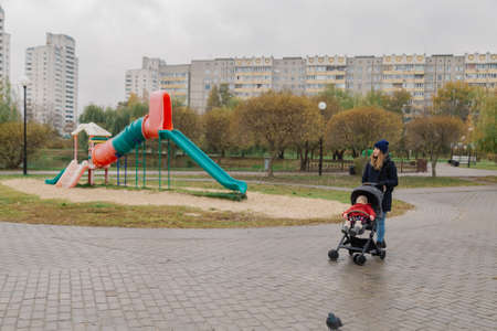 A woman walks in the park with a stroller and a small child.