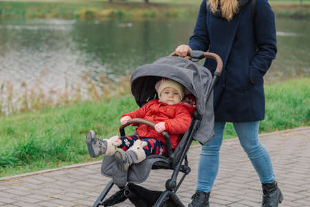 A woman walks in the park with a stroller and a small child near the lake.