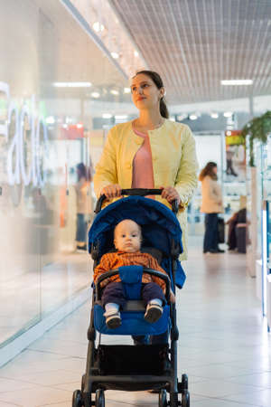 Woman with a baby in a stroller in a mall. Banco de Imagens