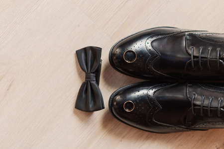 Shoes and a butterfly on a wooden floor, mens wedding accessories.