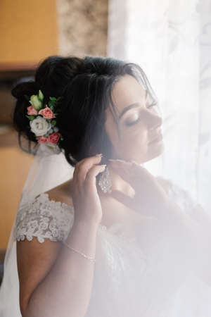 fashion photo of beautiful bride with dark hair in elegant wedding dress and diadem posing in room in the wedding morning.