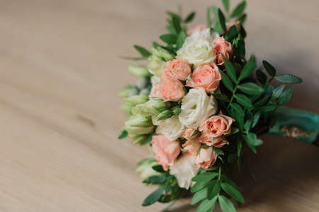 Wedding bouquet lying on grey carpet during preparation before celebration. Side view of decorative rose flowers and leaves bouquet. Marriage decoration of flowers bouquet Stock Photo