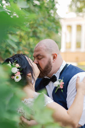 Newlyweds on their wedding day are walking in the park, looking at each other, smiling.